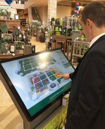 Man in suit using way finder at Nebraska furniture mart